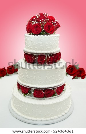Rose covered wedding cake at reception table