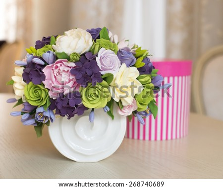 Rose flower bouquet and gift box on wooden table - stock photo