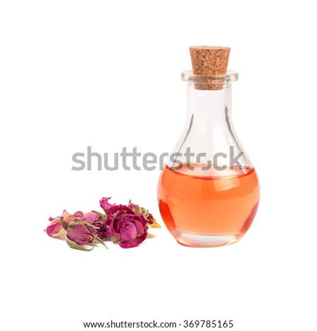 Rose flower petals and buds with aromatherapy essential oil glass bottle isolated over white background - stock photo