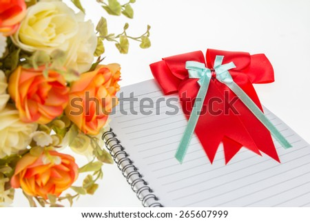 Rose flower plastic and Red ribbons  with tails on note book  on white background