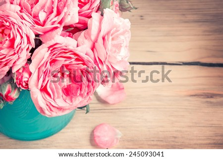 Rose flowers in blue pot on wooden background. Vintage holiday decoration.Mother's day. - stock photo