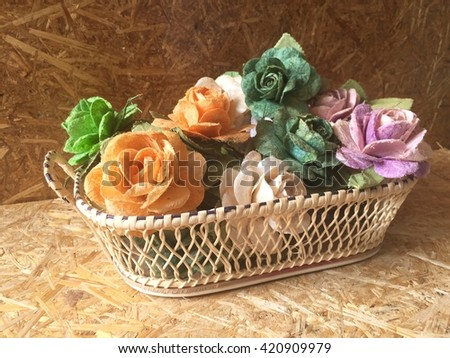 Rose flowers in mulberry paper in basket with lighting at morning - stock photo