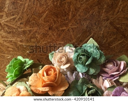 Rose flowers in mulberry paper with wooden texture with lighting at morning - stock photo