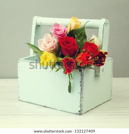 Rose flowers in wooden box - stock photo