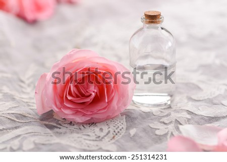 Rose flowers with aromatherapy essential oil glass bottle on silk