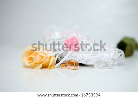 Rose, garter and wedding rings - stock photo