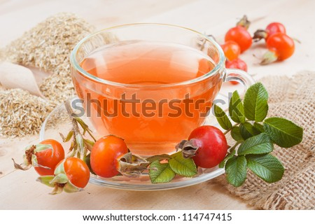 rose hip tea with red berries and chamomile - stock photo