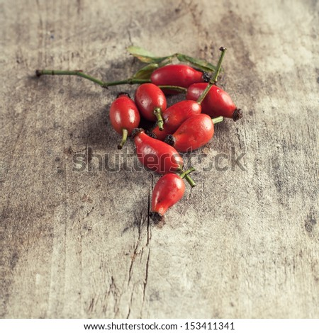 Rose hips on a wooden table, close up photo - stock photo
