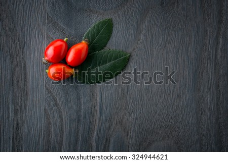 rose hips over Wooden Background - stock photo