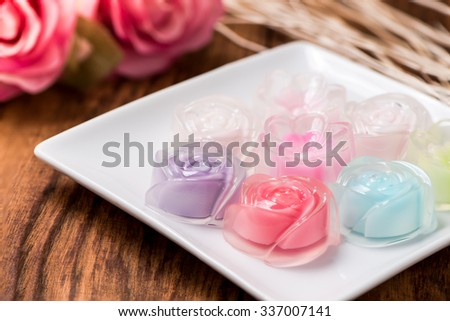 Rose jelly in plate on wood table