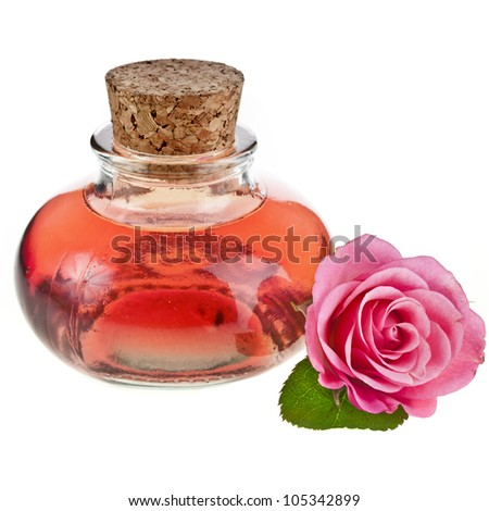 Rose oil in bottle with flower isolated on white - stock photo