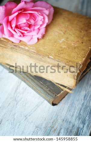 rose on old blue wooden table with old books