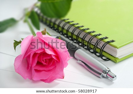 rose pen and notebook on white