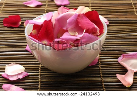 Rose petal floating in water in bowl sitting on bamboo mat - stock photo