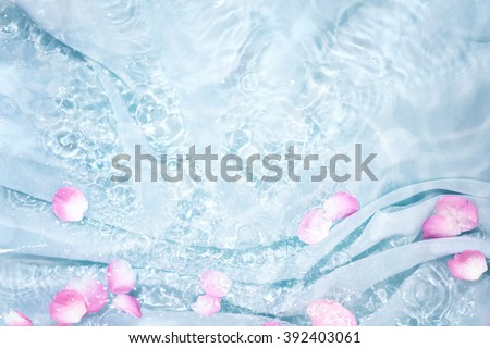 Rose petal in water with soft silk - stock photo