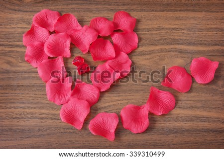 Rose petals on wooden background. Valentine's Day concept - stock photo