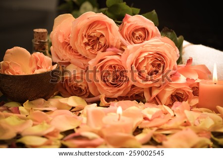 rose petals with rose with candle, towel ,oil   - stock photo