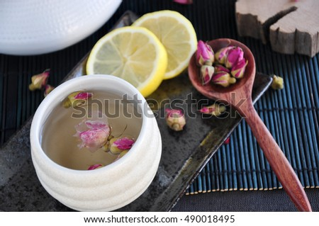 Rose tea cup with dried roses and lemon on black tray