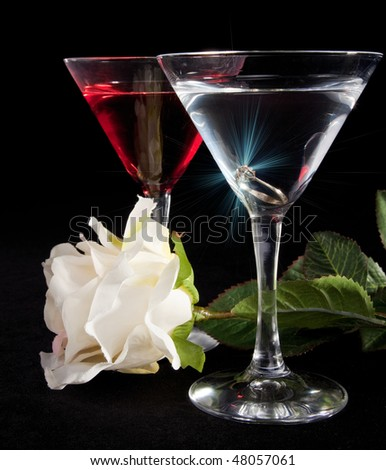 Rose, two glasses of cocktails and engagement ring with a diamond - stock photo