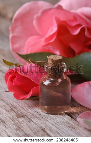 Rose water in a glass bottle on a background of pink roses close up vertical  - stock photo