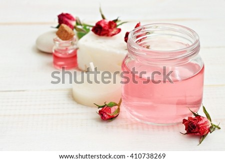 Rose water in jar, dried roses, candle, relaxing aromatherapy. Soft focus, soft light. - stock photo