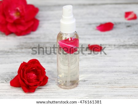 Rose water with a rose petal inside surrounded by rose flowers