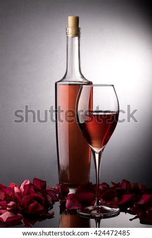 Rose wine glass, rose wine bottle ans rose petals - stock photo