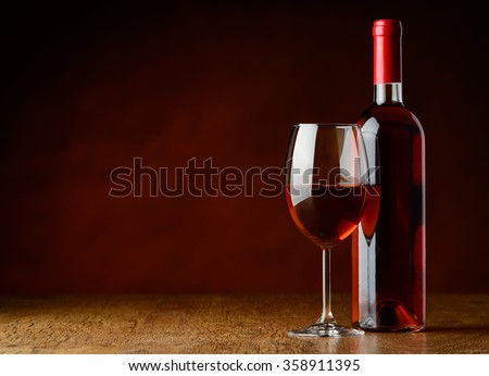 Rose wine on a wooden table and on dark background - stock photo