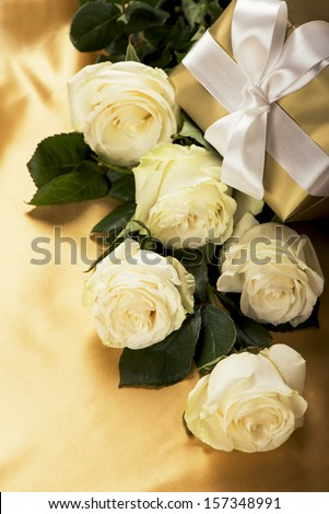 Rose with gift box on gold background