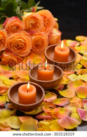 Rose with many rose petals with row of candle in bowl  - stock photo