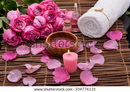 Rose with rose petals, salt in wooden bowl ,candle on mats - stock photo
