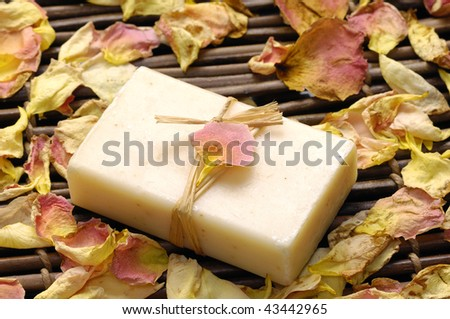 rose withered petals and soap on bamboo mat - stock photo
