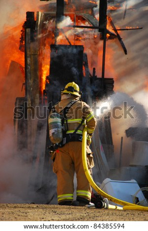 ROSEBURG, OR - SEPTEMBER 03: Single fire fighter spraying a straight steam into a fully involved shop fire off of Breezy Lane, September 03, 2011 in Roseburg, OR - stock photo