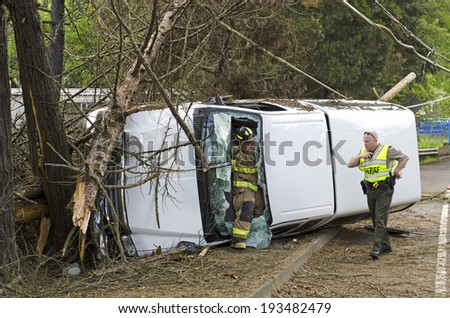 ROSEBURG, OR, USA - APRIL 25, 2014: Fire fighters and police at a single vehicle accident that rolled and hit a power pole and trees resulting in minor injuries to the driver.