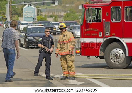 Roseburg, OR, USA - April 2, 2015: Firefighters respond to a two vehicle accident with on car on fire. - stock photo