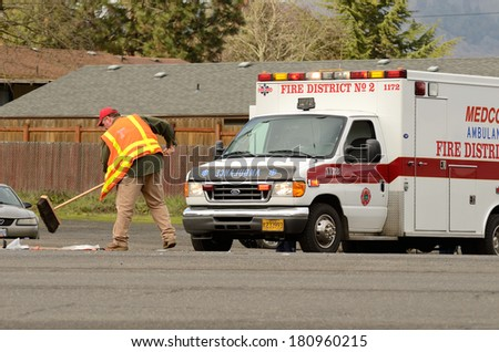 ROSEBURG, OR, USA - JANUARY 13, 2014:  Emergency responders at the scene of a motorcycle vs car at a busy intersection that left the rider with serious injuries. - stock photo