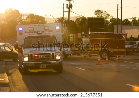 ROSEBURG OR, USA - JULY 12, 2014: Roseburg Oregon Police and Fire deparment at the scene of a single car accident that knocked over a fire hydrant, July 12, 2014 - stock photo