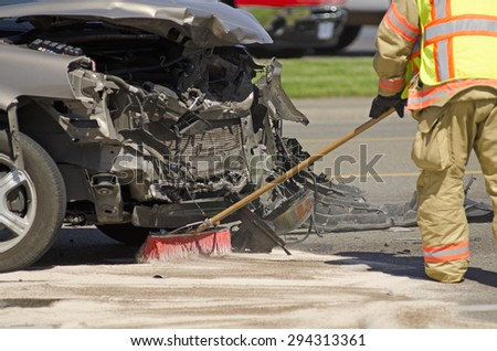 ROSEBURG, OR, USA - June, 10, 2015: A fire fighter cleans up fluids at the scene of a two vehicle accident with heavy head on damage - stock photo
