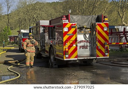 Roseburg OR, USA - March 26, 2014: Fire engine and pump operator engineer on a structure fire of a mobile home - stock photo