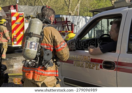 Roseburg OR, USA - March 26, 2014: Fire incident commander fire chief discussing operations with firefighters on a structure fire of a mobile home - stock photo