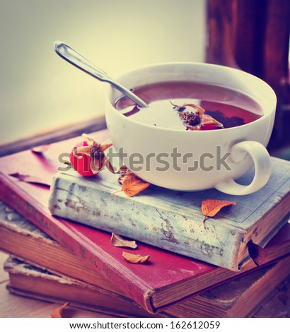 rosehip tea on old books/tea home with books/romantic autumn vintage background with books and tea/cup of tea with hip roses on wooden table - stock photo