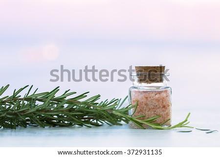 Rosemary aromatherapy salt in bottle on sunset - stock photo
