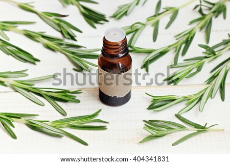 Rosemary essential oil. Fresh rosemary herb sprigs scattered, apothecary bottle. - stock photo