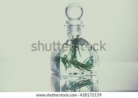 Rosemary essential oil in a glass bottle, Aroma oil - stock photo
