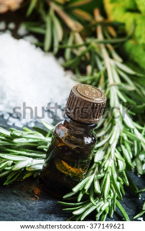 Rosemary essential oil Spa composition with sea salt, candles, towels and a fresh branch of rosemary on a wet dark background, selective focus - stock photo