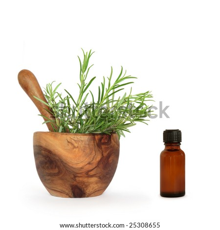 Rosemary herb leaves in an olive wood mortar with pestle and aromatherapy brown glass bottle over white background.