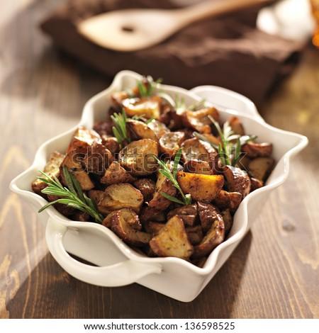 rosemary herb potatoes in white baking dish. - stock photo