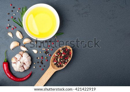 Rosemary, olive oil, pepper in a spoon, chili and garlic on a dark stone. Ingredients for cooking. Spices background with copy space. Top view - stock photo