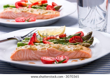 Rosemary roasted salmon served with asparagus, cherry tomatoes, red bell pepper topped by mustard rosemary sauce and glass of ice water for healthy style dinner - stock photo