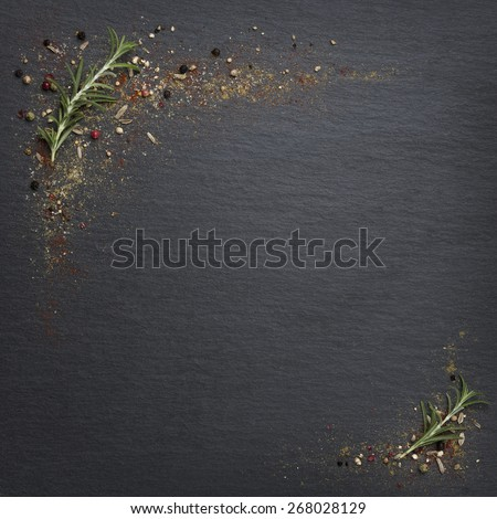 Rosemary with mediterranean spices framing a dark slate stone slab with empty copy space. - stock photo